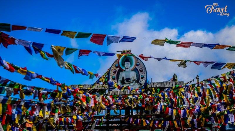 Buddha Statue with prayer flags at Mandala Top