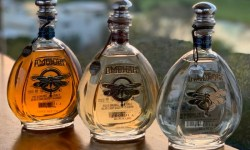 Three bottles of Ambhar tequila, plata, reposado, and anejo