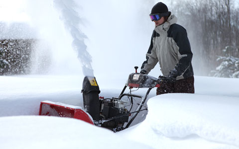 Person using snow blower to remove snow from sidewalk