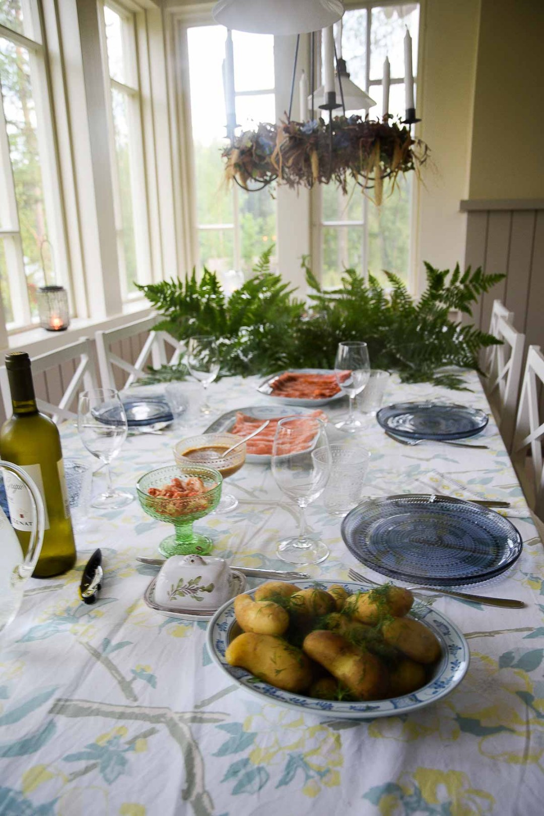 A lovely dining room table in Finland with wine, potatoes, and salmon.