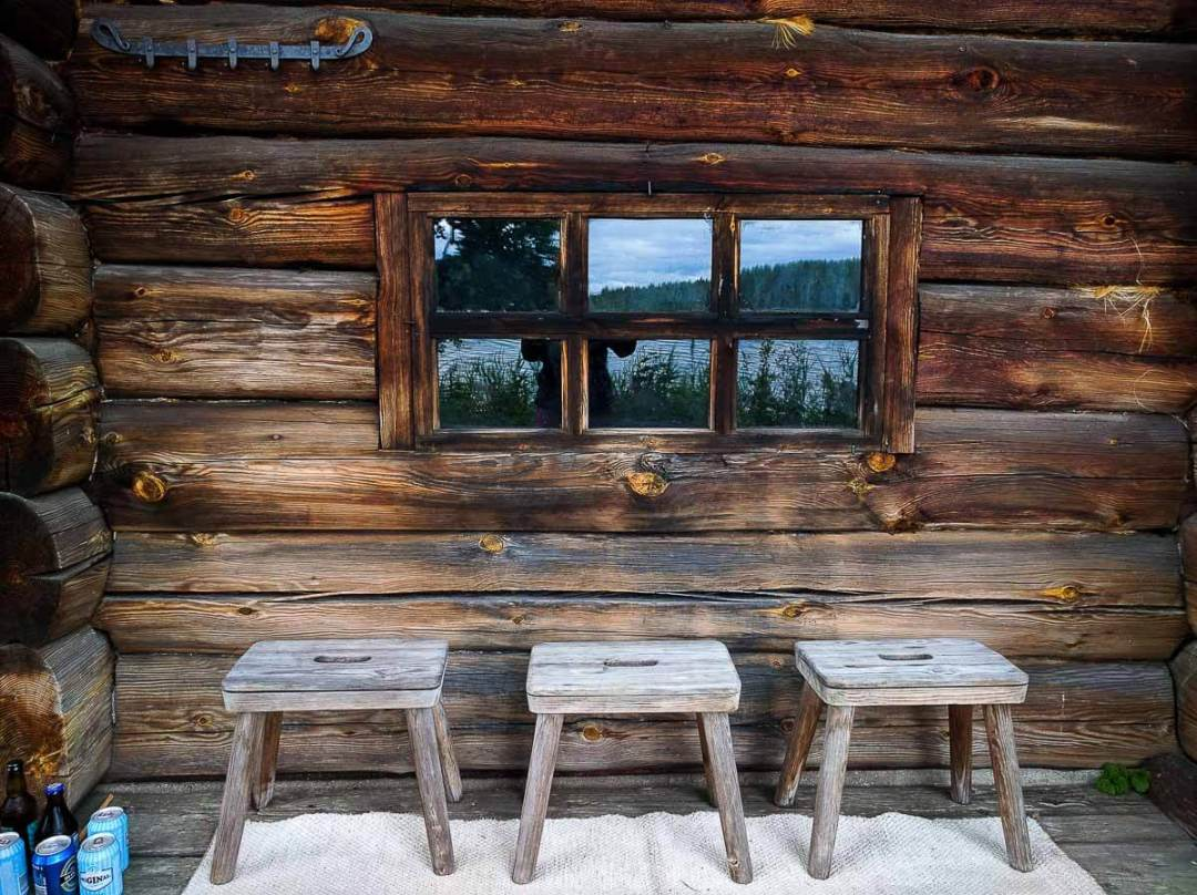 A wooden smoke sauna exterior with three stools and cold drinks.