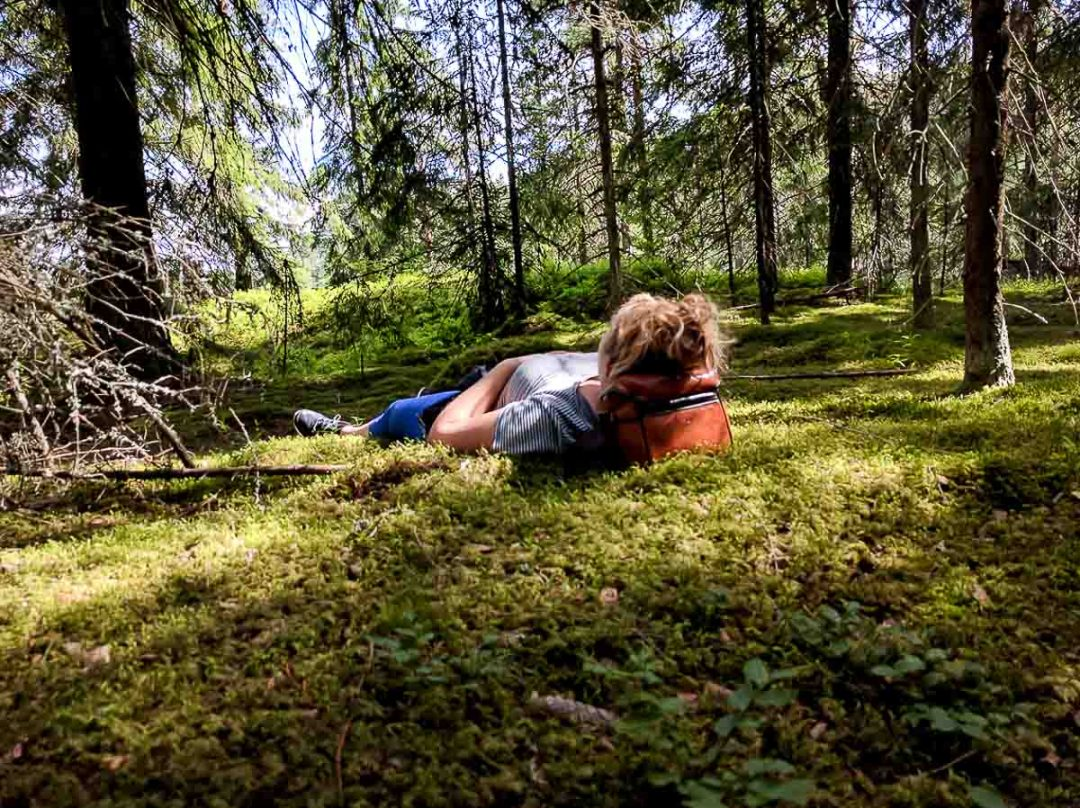 woman laying down on the moss floor of the forest in Finland