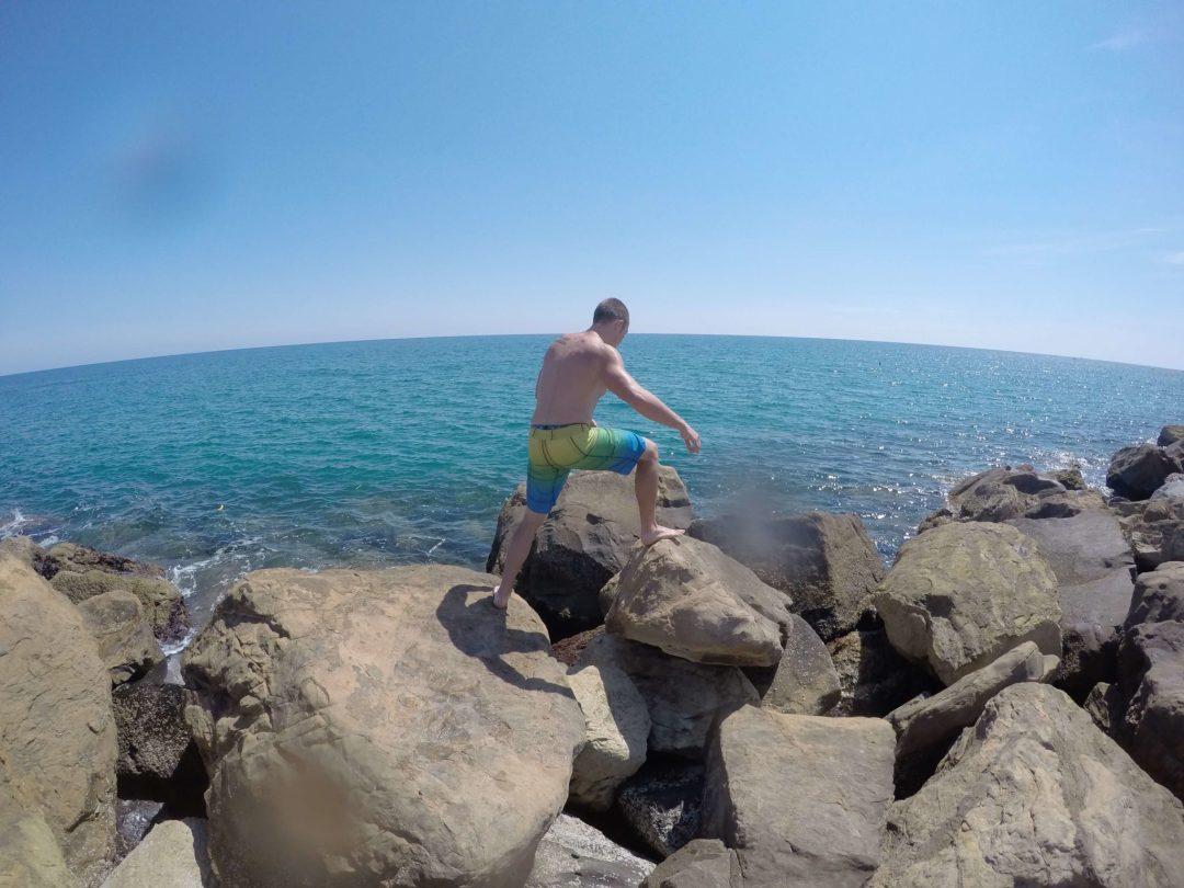 Strong teenage boy running on the boulders at Santa Marinella Beach, Italy.