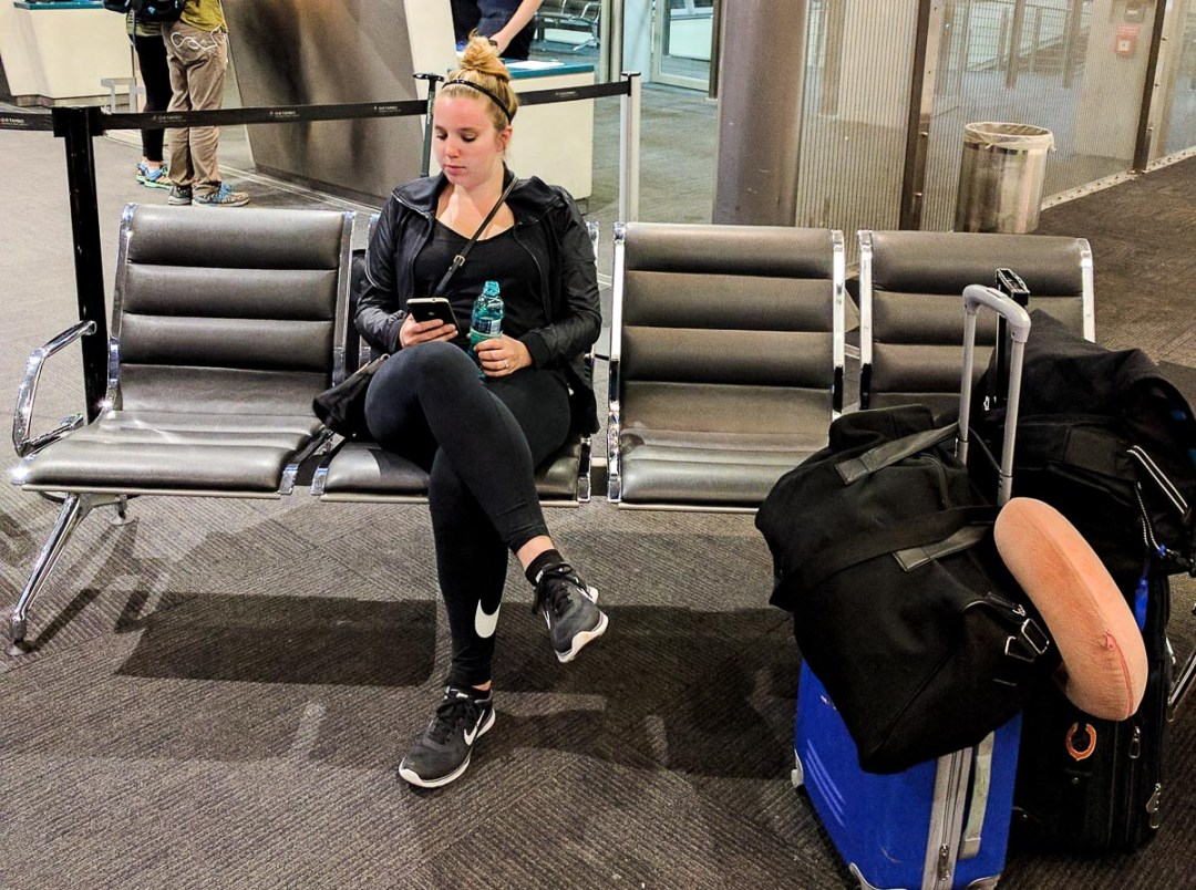Woman sitting in an airport waiting area looking at her phone