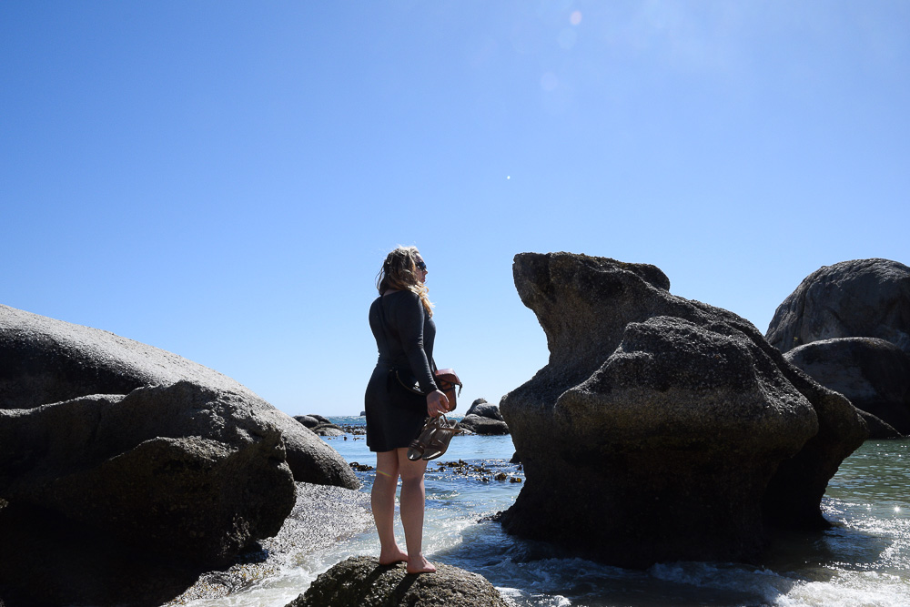 woman standing on a boulder at boulders beach