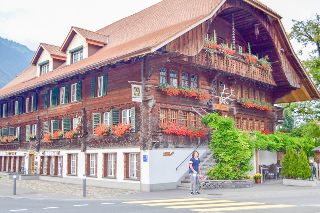 Young man in front of a traditional style hotel in interlaken