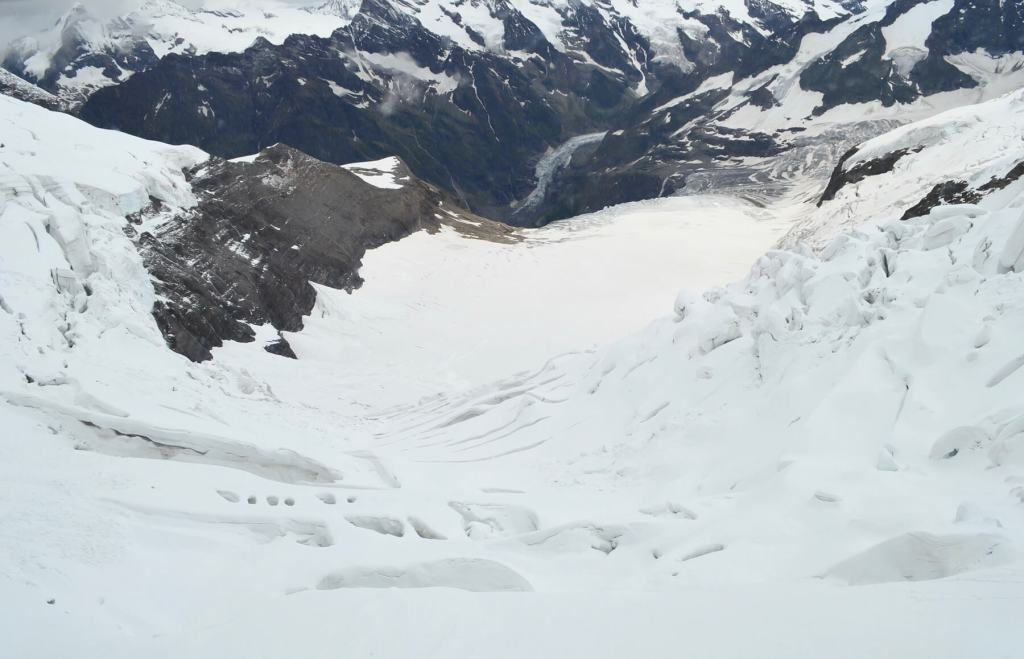 Looking down the side of the mountain at lots of snow and glaciers down below