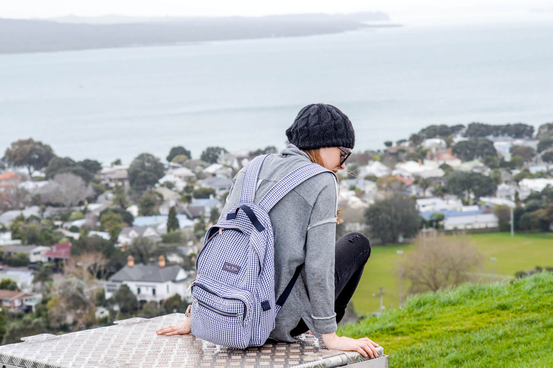 Girl sitting on a box at the top of a hill, with the ocean and town houses behind
