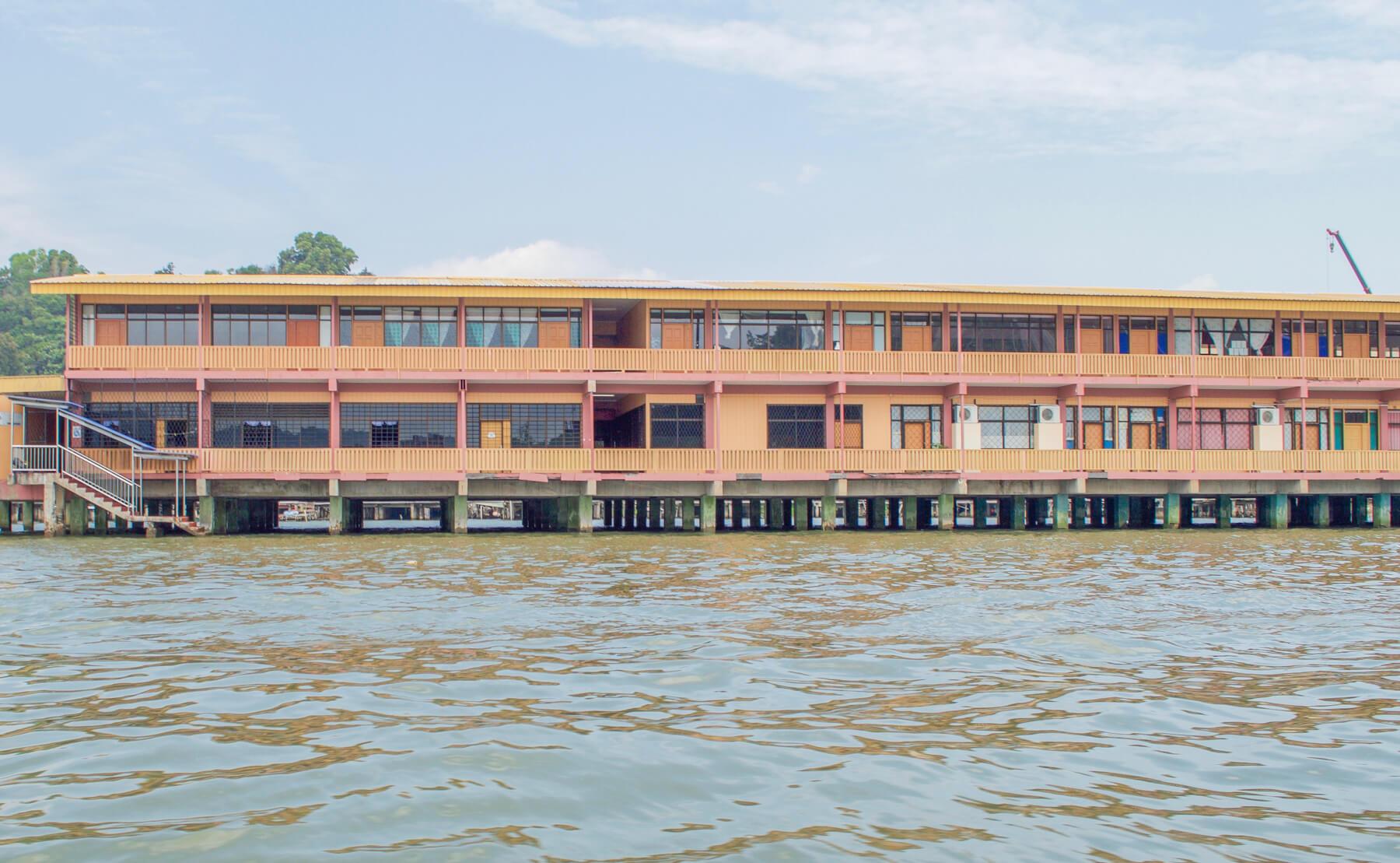 An orange building over the water - Brunei Water Village School
