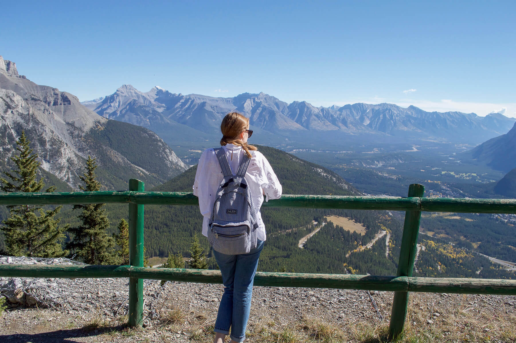 Girl looking at the view from the top of a mountain in Banff