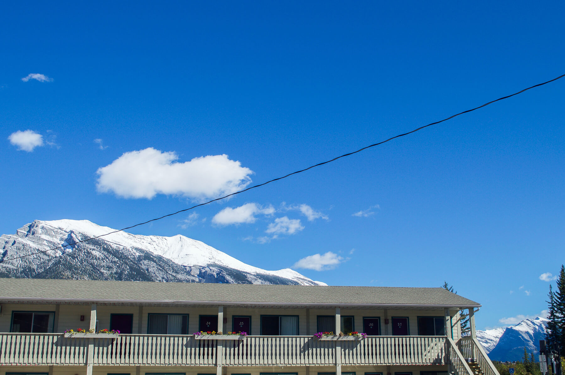 The top floor of a motel with the snowy mountains peeking behind it