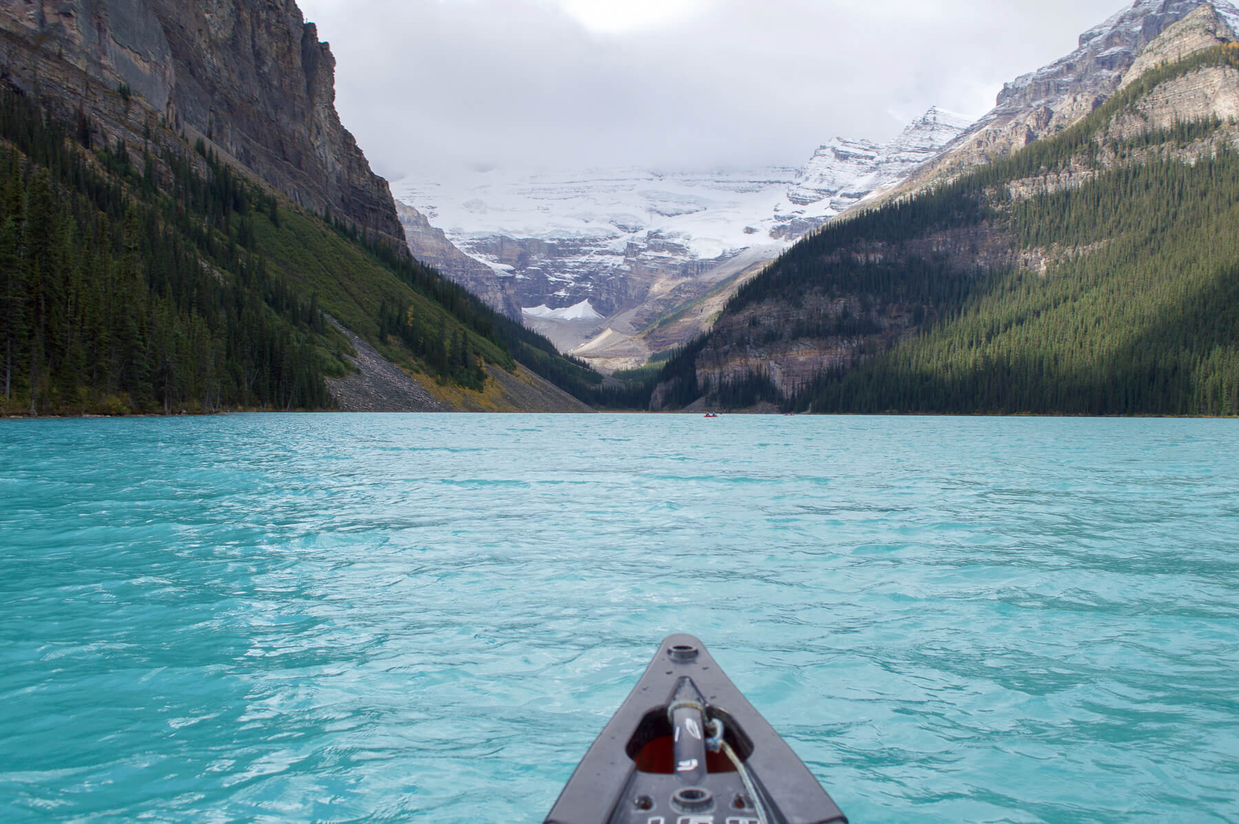 The tip of a canoe on the bright blue water of Lake Louise