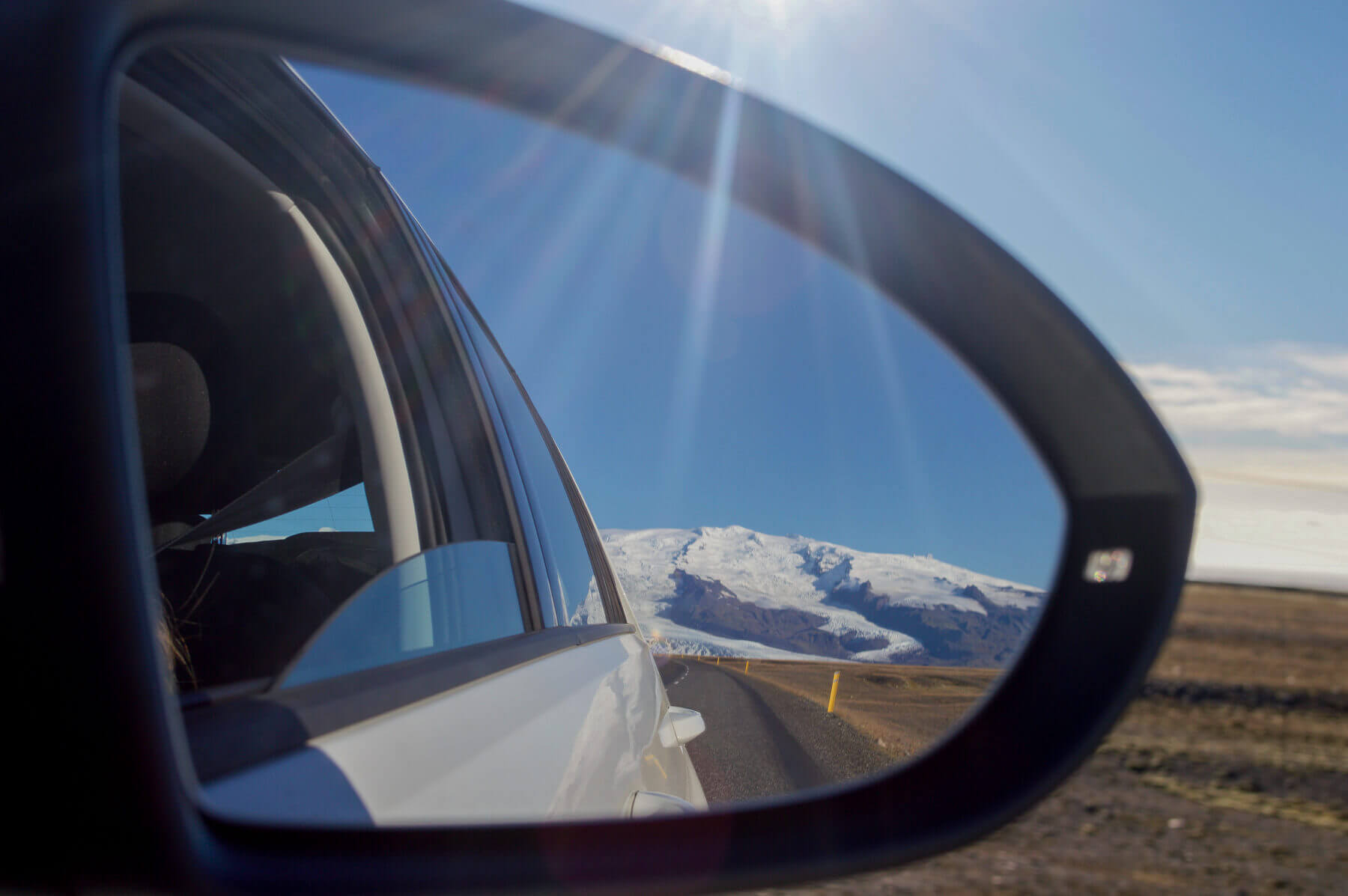 Glacier and Mountains in the mirror of a car