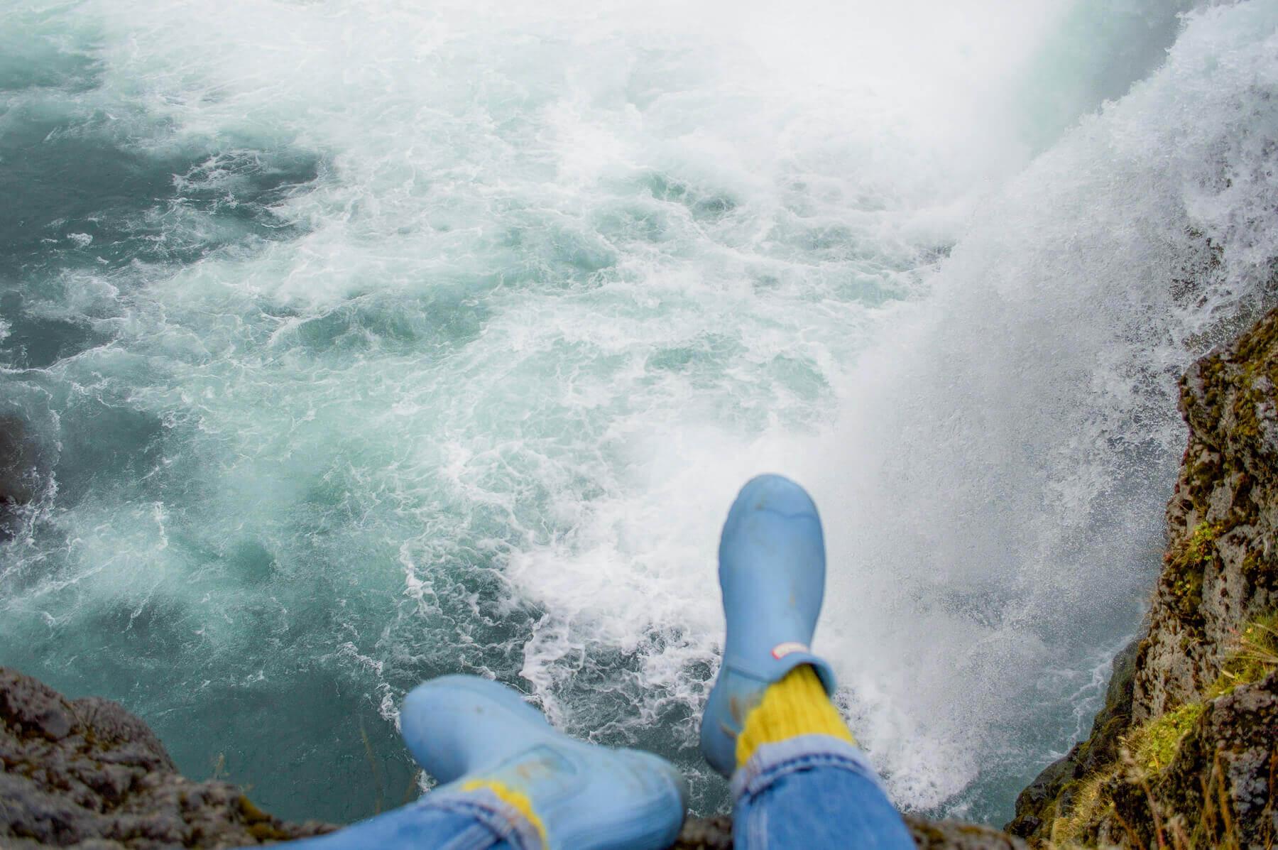 feet hanging over edge of waterfall