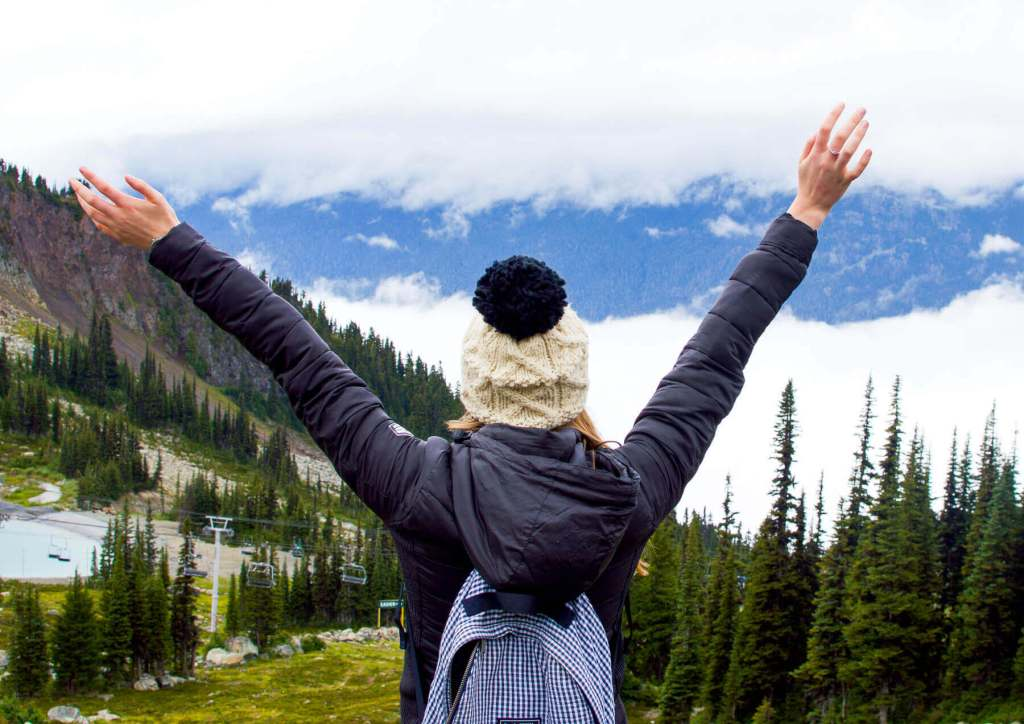 Girl wearing white beany, on top of mountain with hands in the air