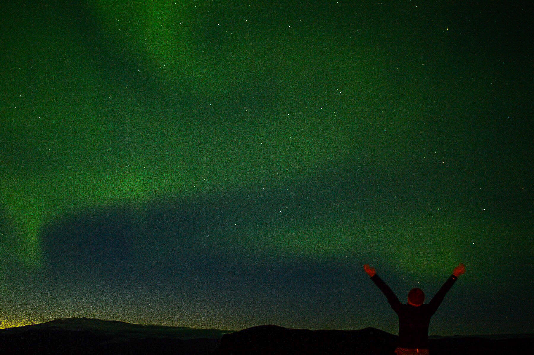 A girl with her arms up in front of the Northern Lights