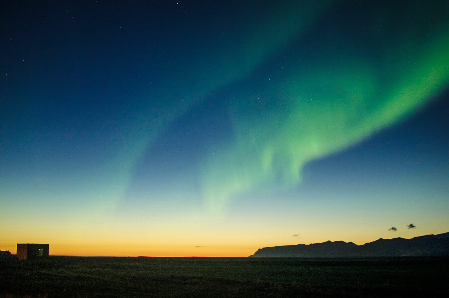 The green northern lights in the sky above the sunset