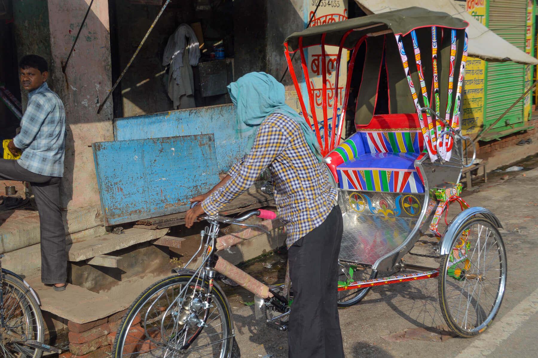 man pushing colourful bicycle rickshaw