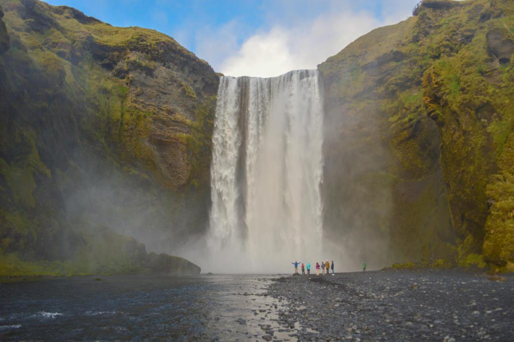 Distant view of people standing infront of Skogafoss Waterfall