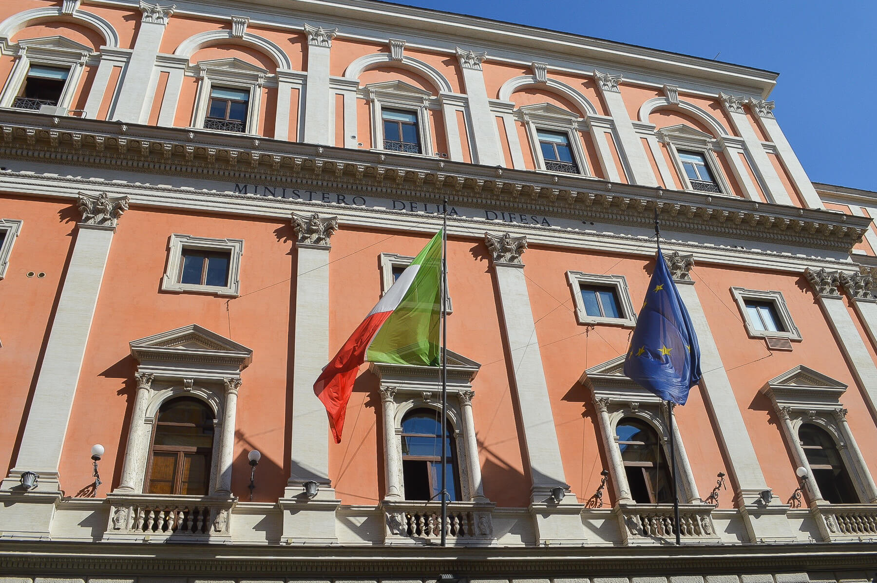 Orange italian building with italy and europe flag