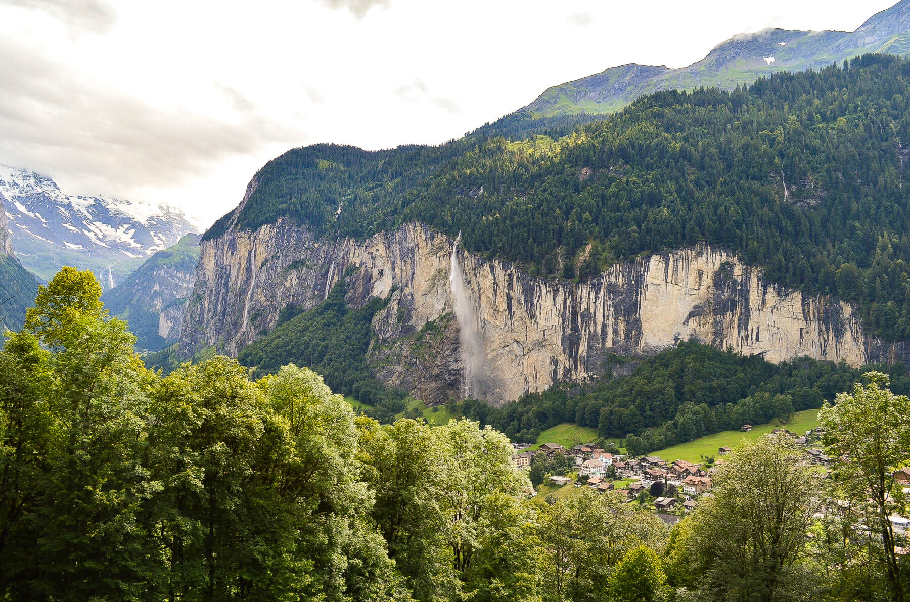 Lauterbrunnen Valley with waterfall pouring from cliff, small town and mountain peaks