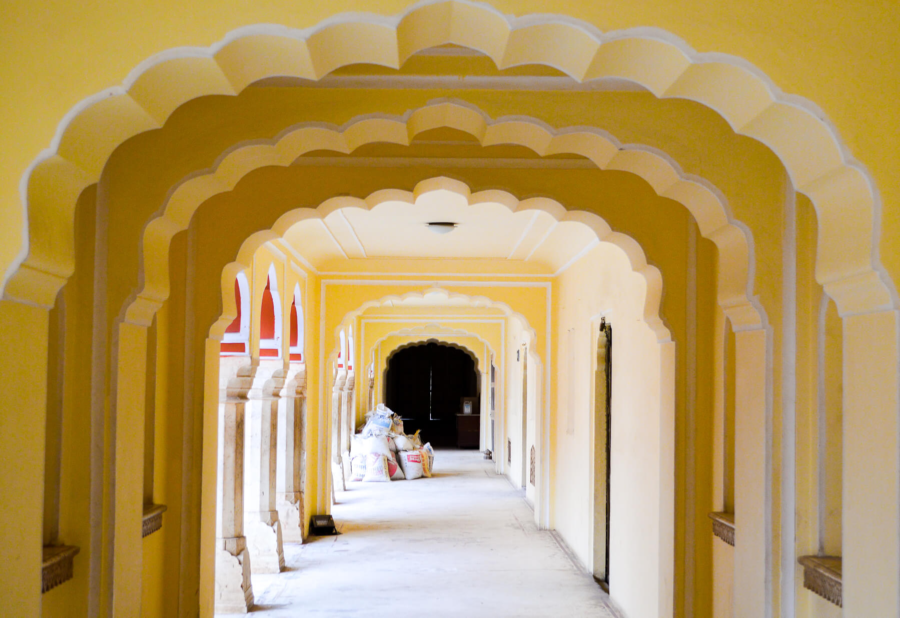 Looking through bright yellow archways of a corridor
