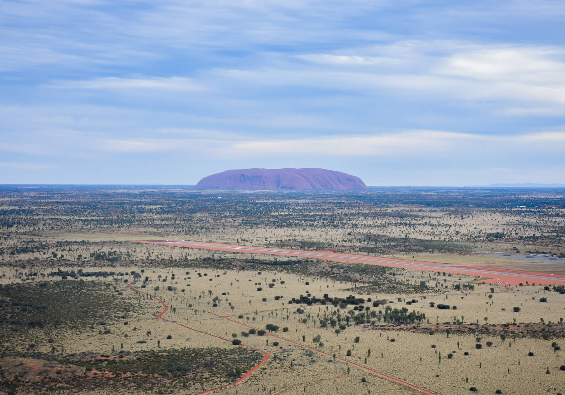 Ayers rock in the distance surrounded by flat grounds - Airport runway in the foreground