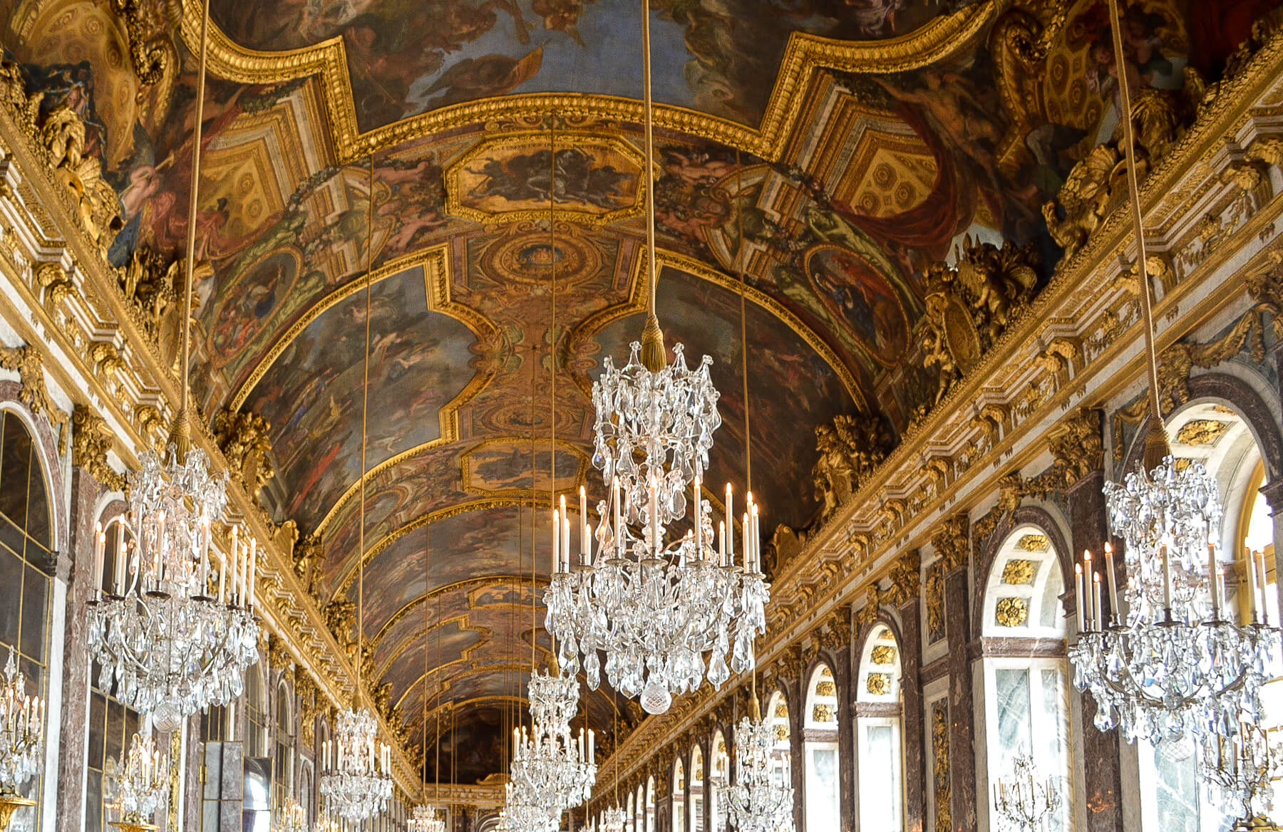 Roof of a hallway plated in gold with ancient painting and chandeliers