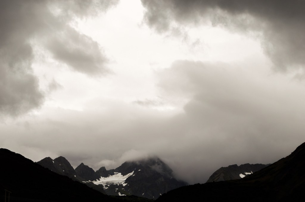 Black rocky mountains in Alaska, with black clouds framing the image