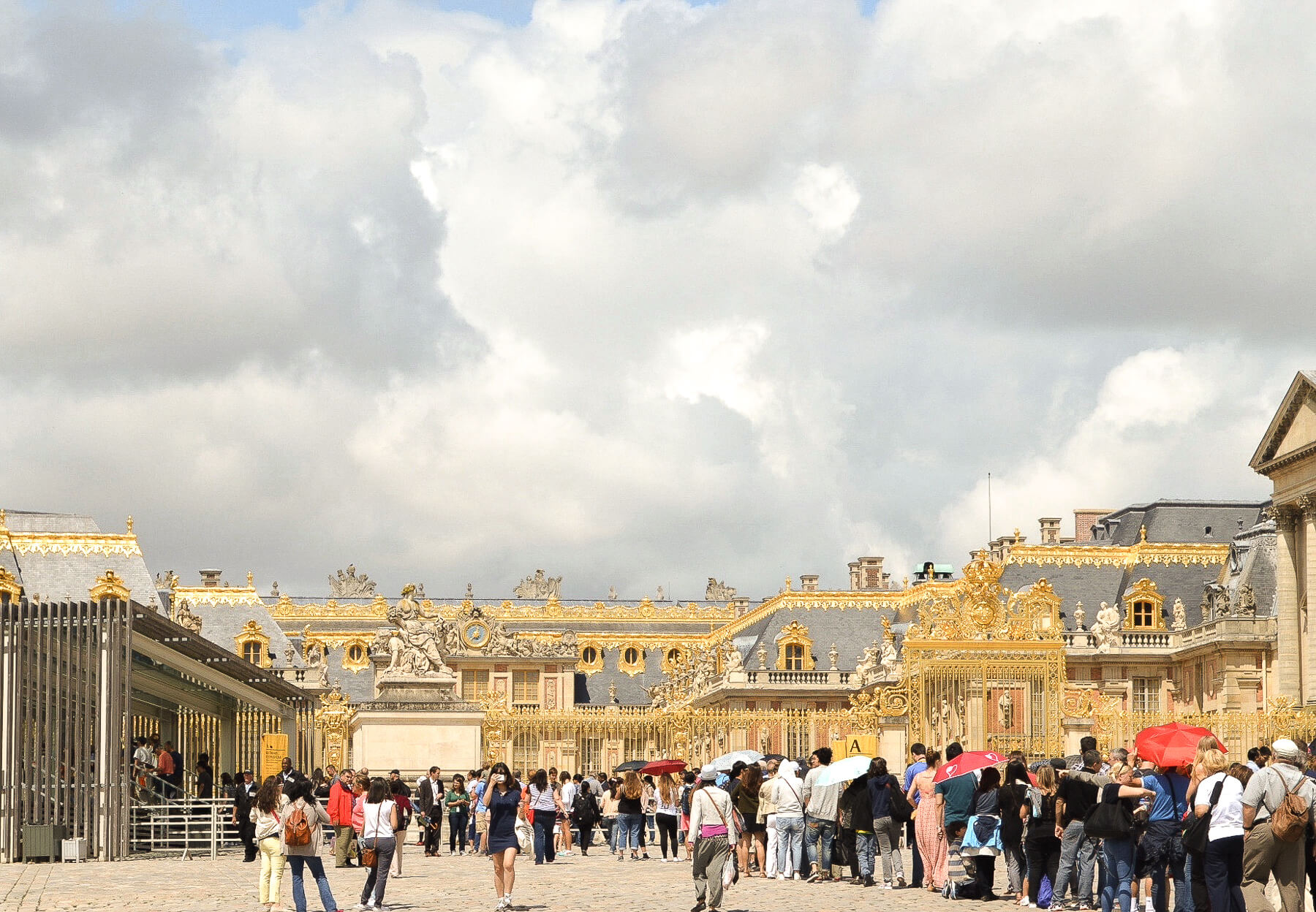 Long queue of people waiting to enter a beautiful golden palace - Palace of Versailles
