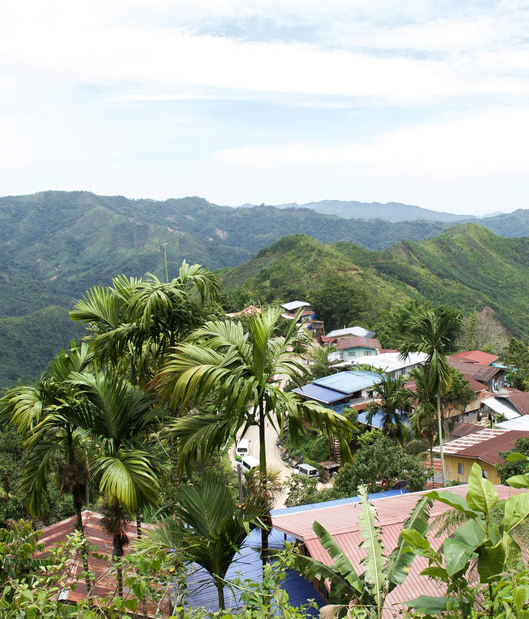 Village along the bridge of a mountain top - distant hills and jungle in the background