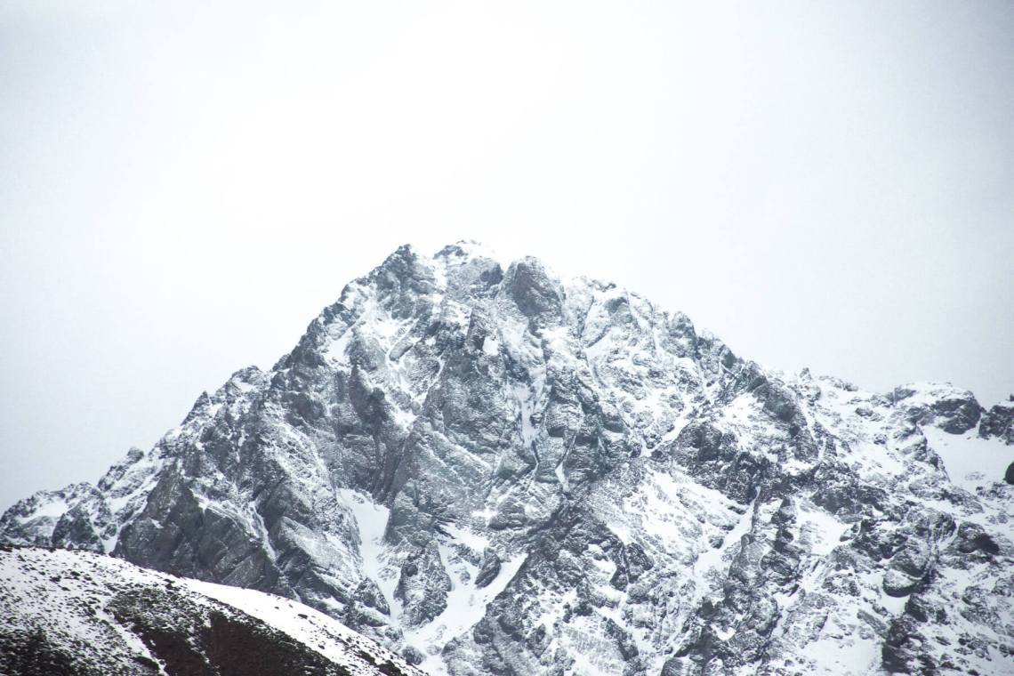 Grey, rocky mountain peak - covered in light snow