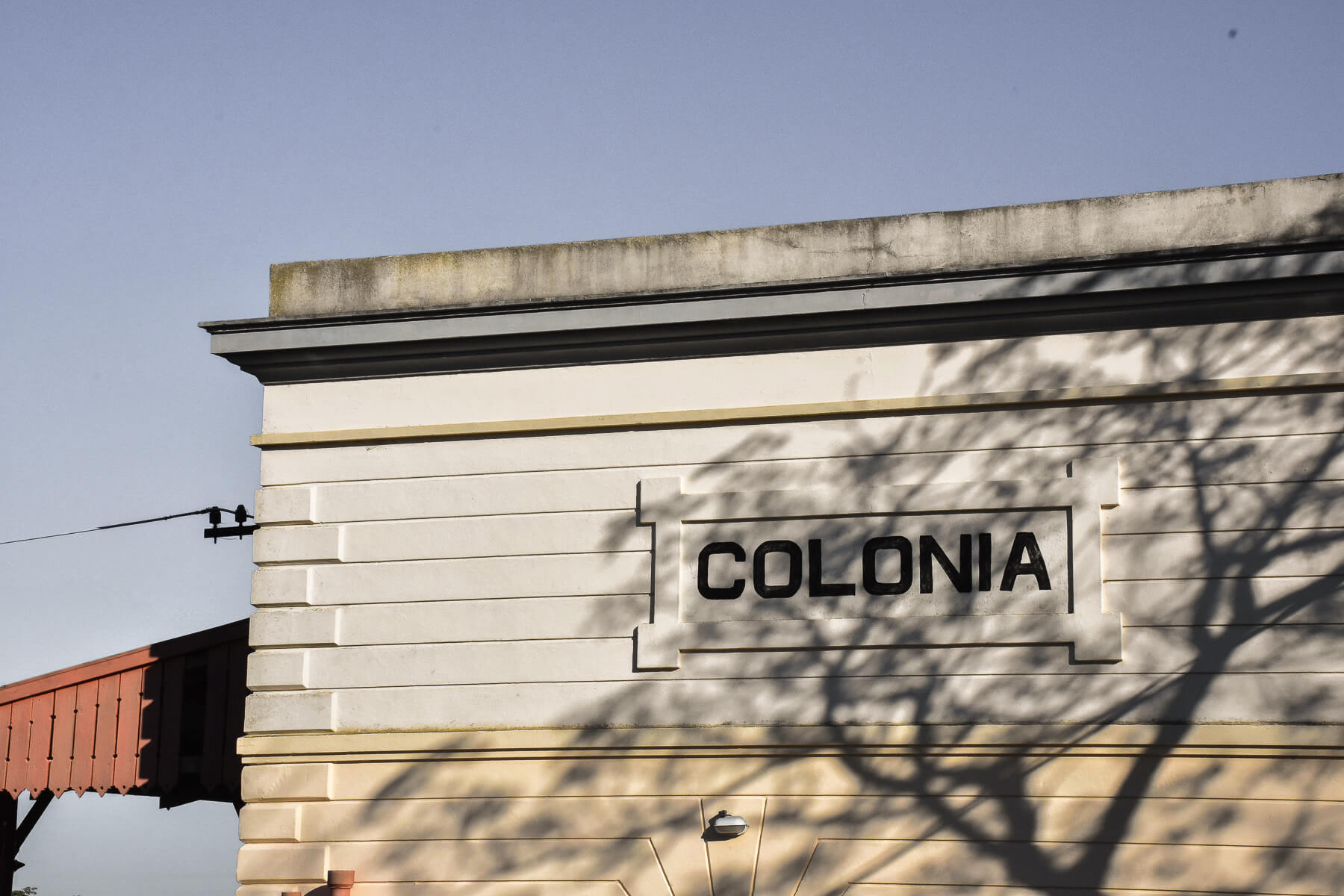 Old wooden building (railway station) with 'Colonia' sign on the exterior