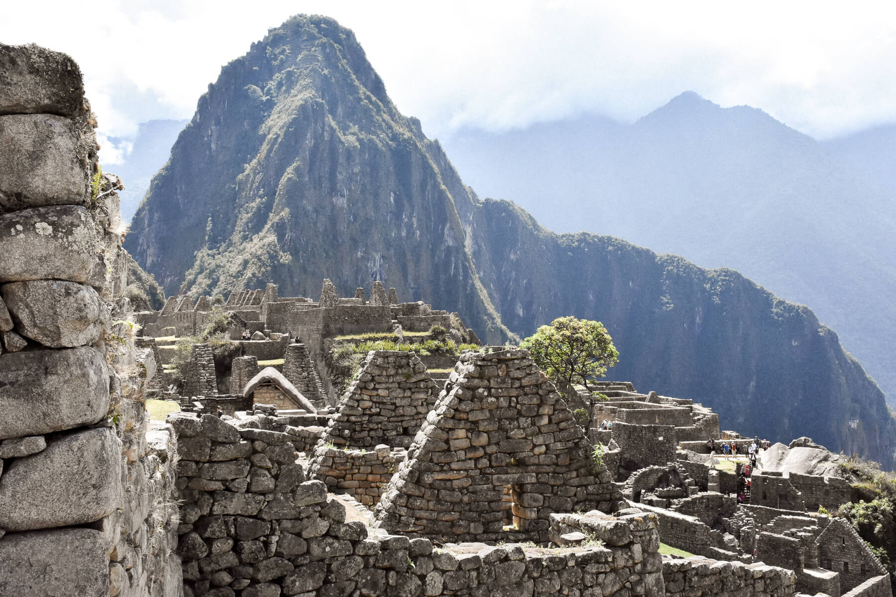 Close up of the Machu Picchu ruins - stone walls and temples with mountains behind