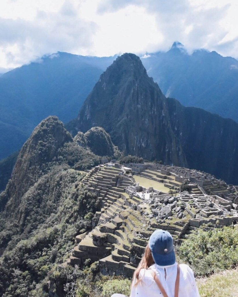Girl in blue hat over looking Machu Picchu and ruins
