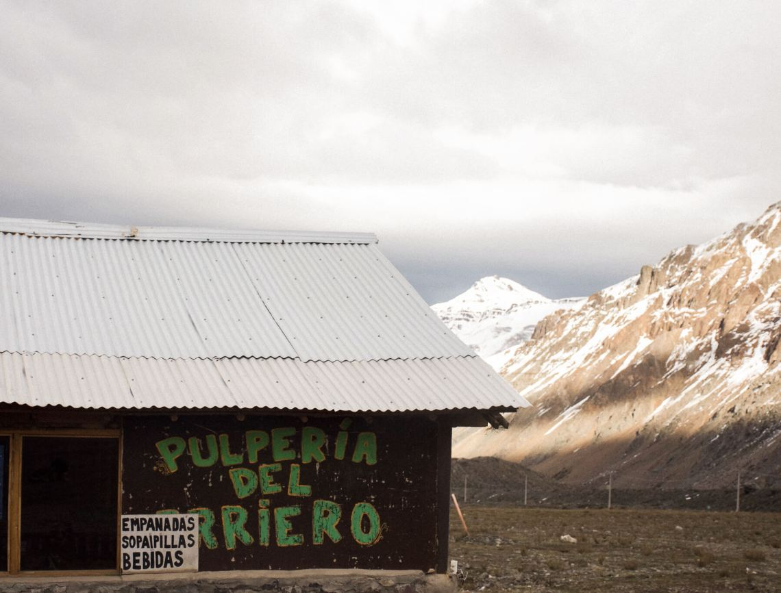 """A building with sign """"PULPERIA DEL ARRIERO"""" - rocky mountains in the background"""