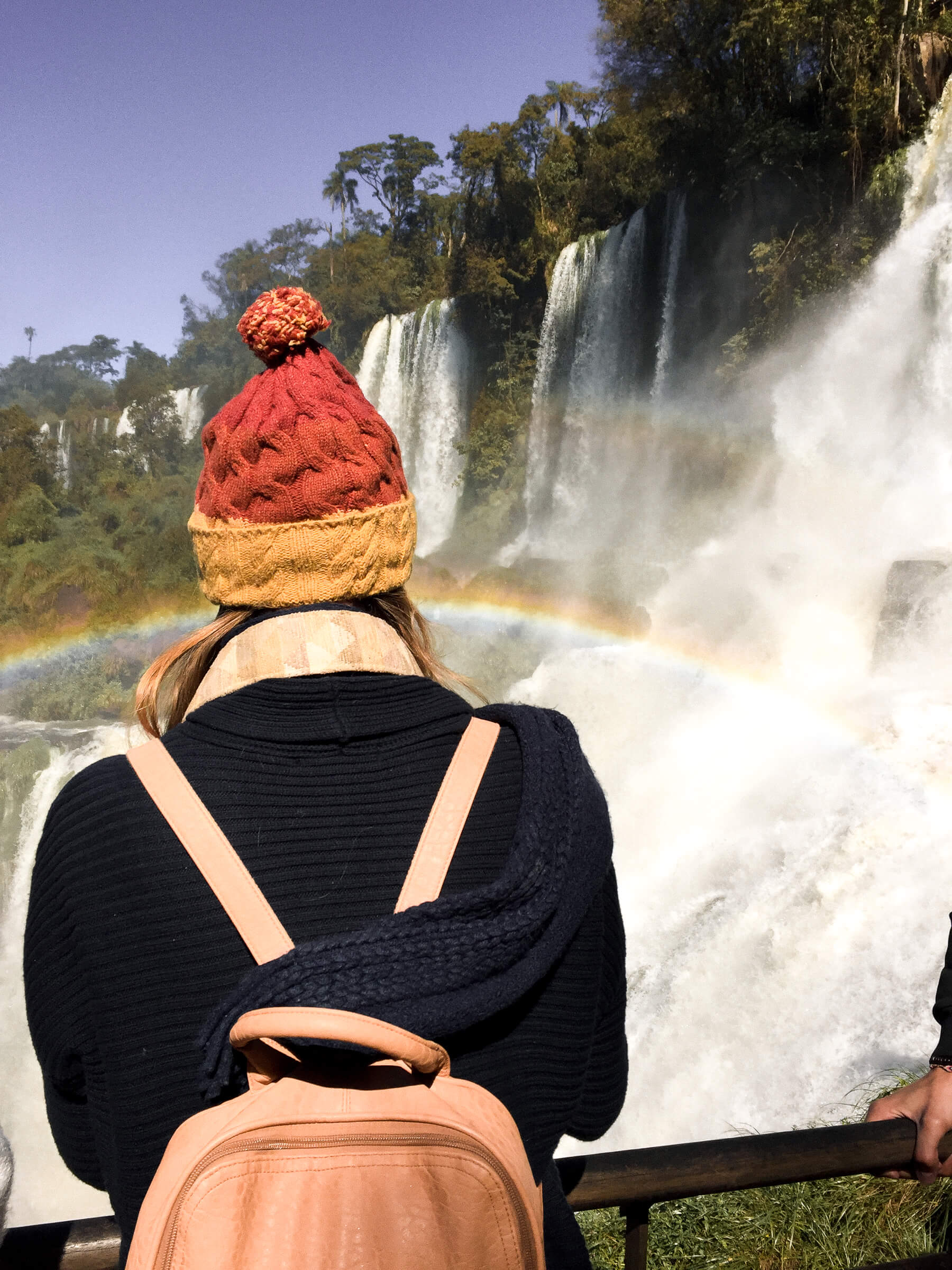 A girl wearing a red beany over looking a huge waterfall with a rainbow arching in front