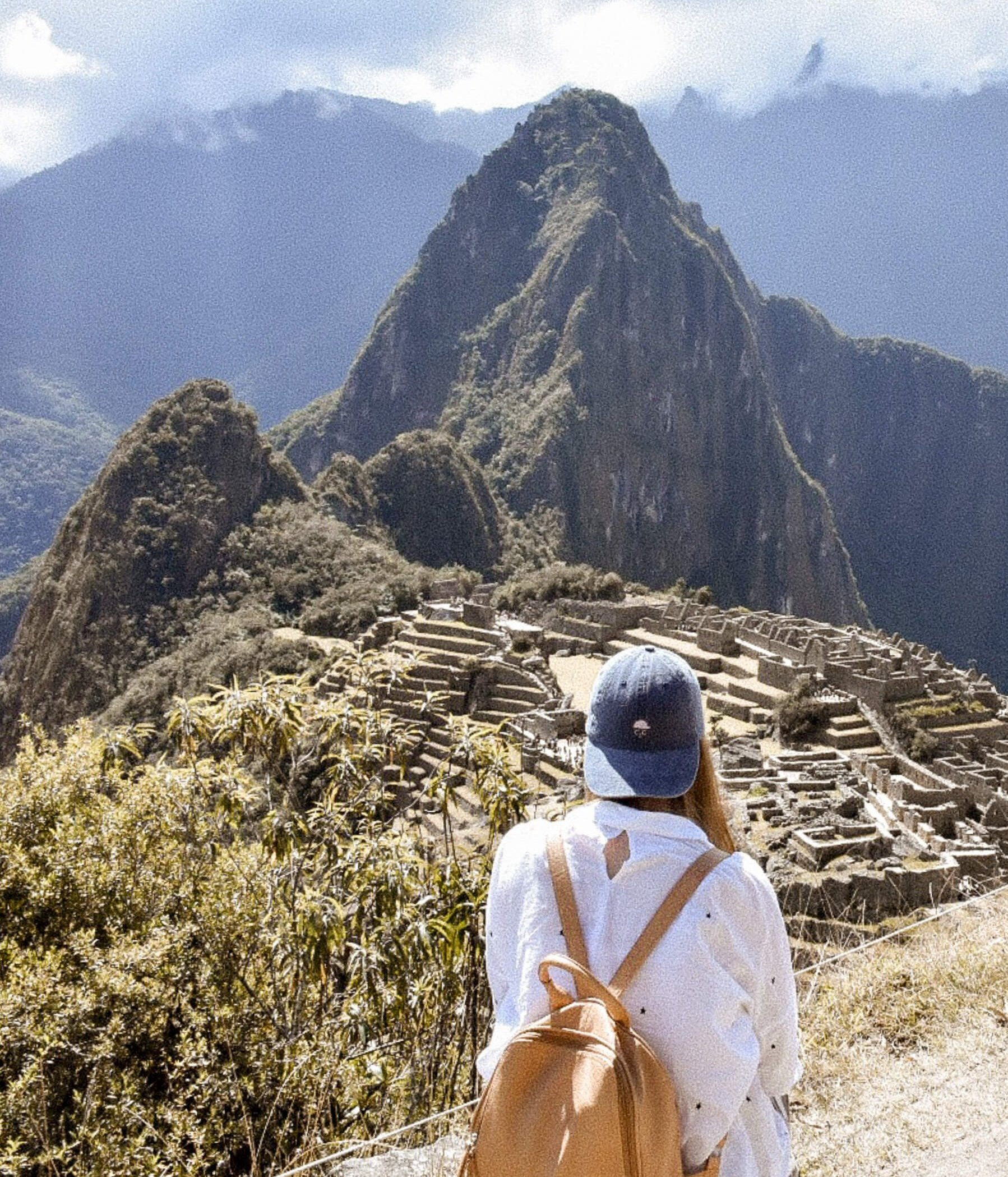 Girl overlooking Machu Picchu and ruins from high above