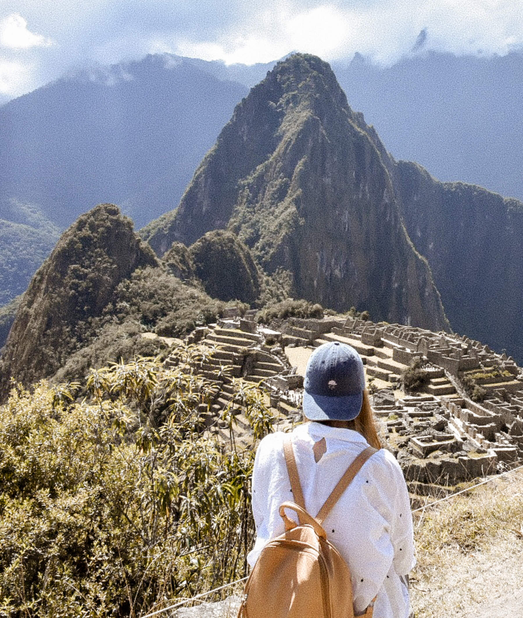 Girl with a backwards facing denim cap overlooking Machu Picchu and ruins