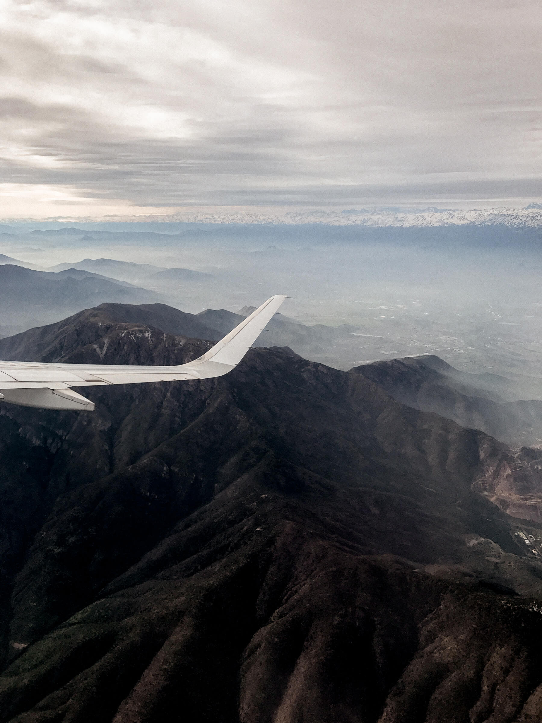 The wing of a plane whilst flying above dark, rugged mountains