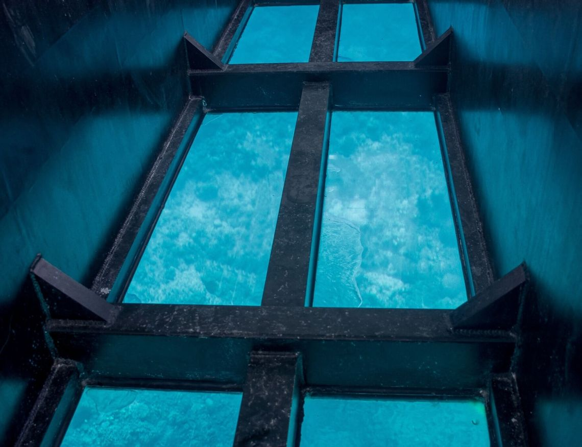 Looking down through the glass bottom of a boat at blue water and coral (things to do in Vanuatu)