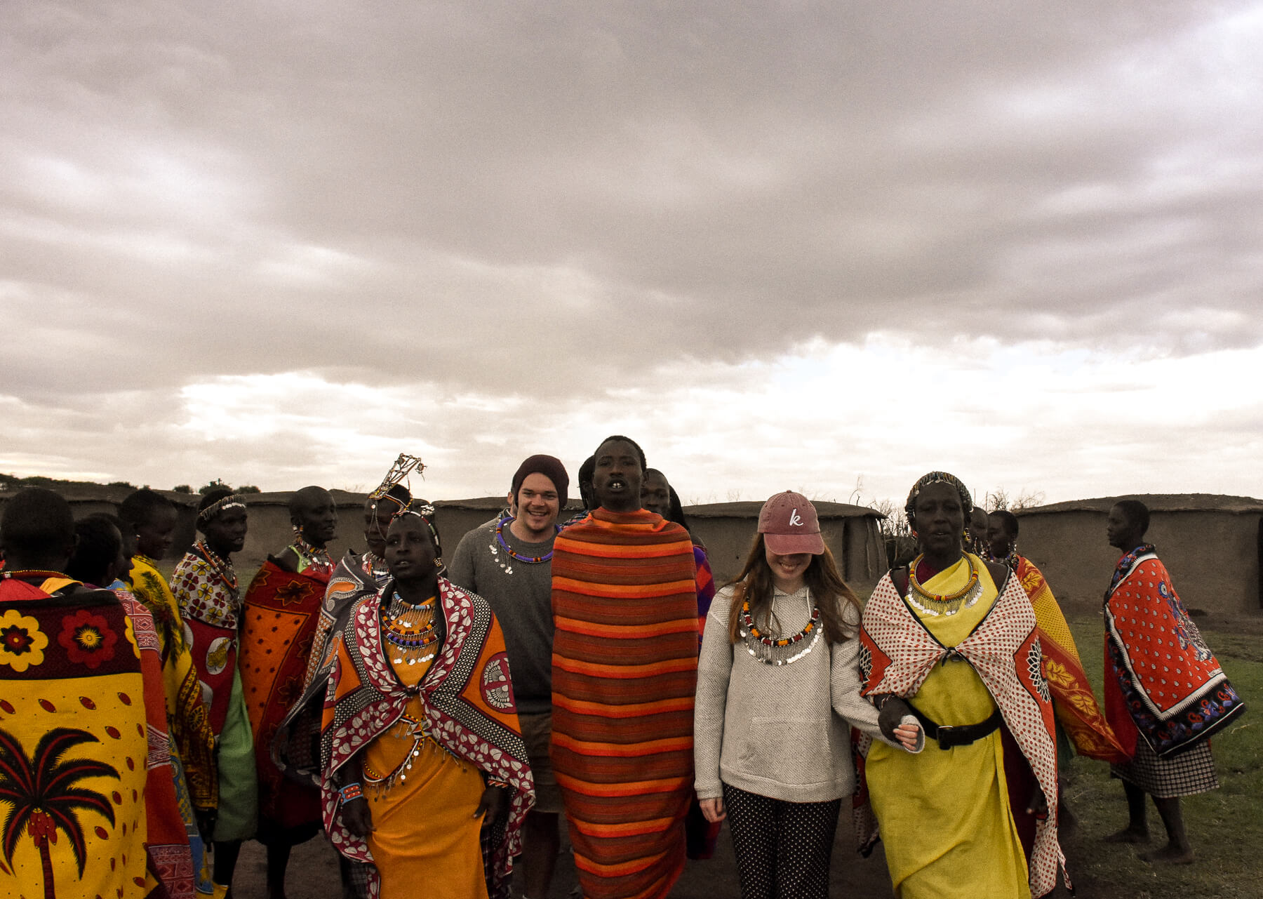 2 tourists (one woman and one man) walking towards the camera with a group of Maasai during a cultural dance