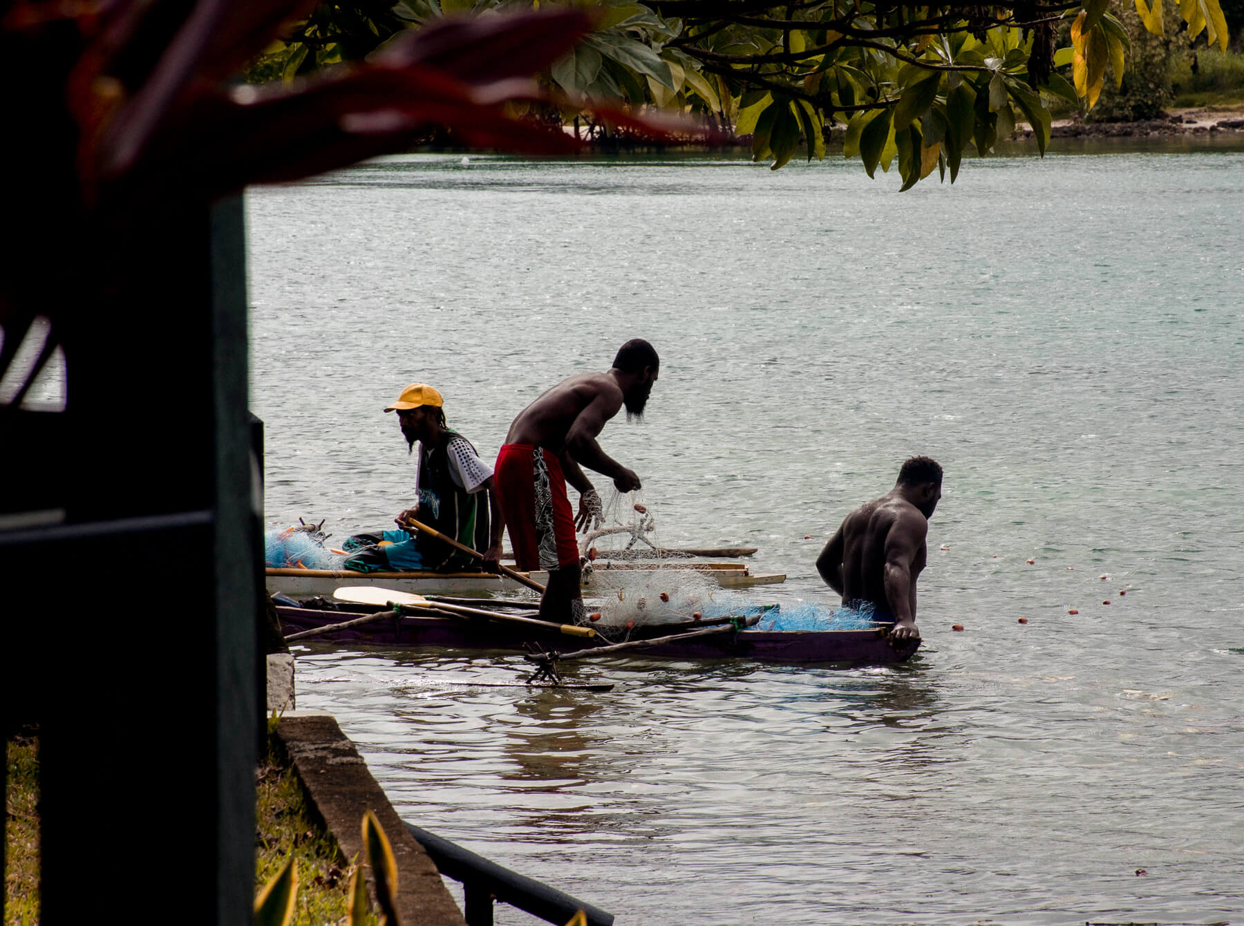 3 men from a local Vanuatu village in a traditional canoe, catching fish with a net