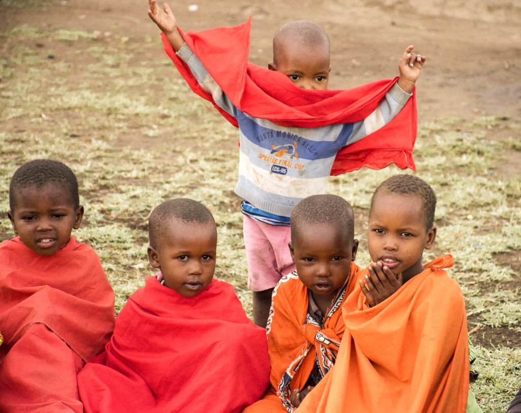 Young kenyan children from the Maasai tribe sitting on the grass