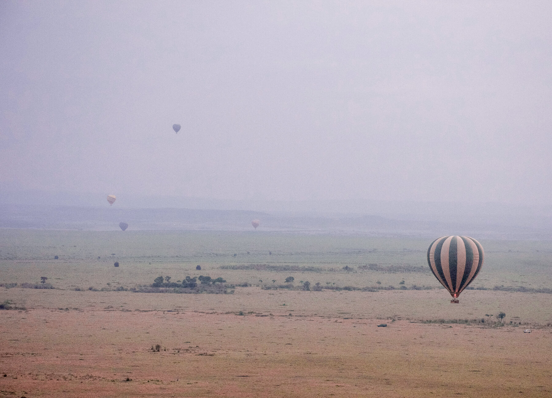 A green and yellow hot air balloon flying low, with 4 other balloons flying far in the distance