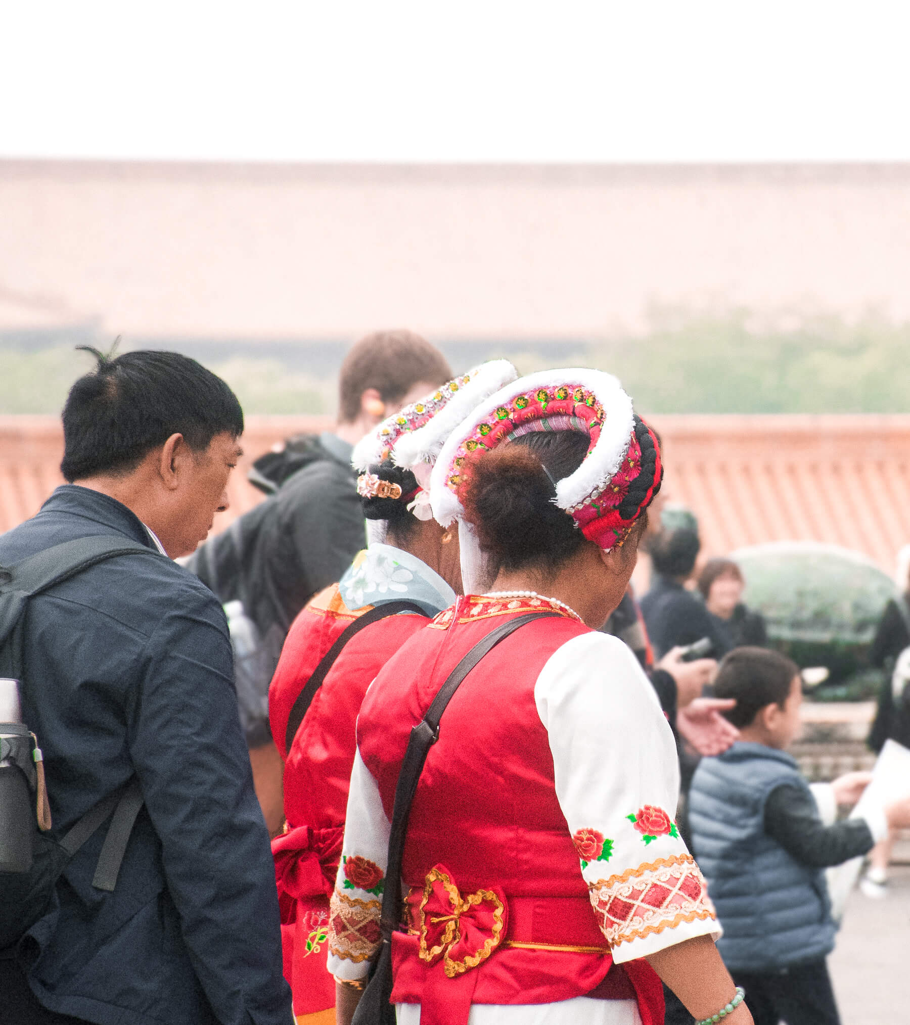Chinese ladies walking away from the camera in traditional red Chinese outfits, wearing a white and red headpiece