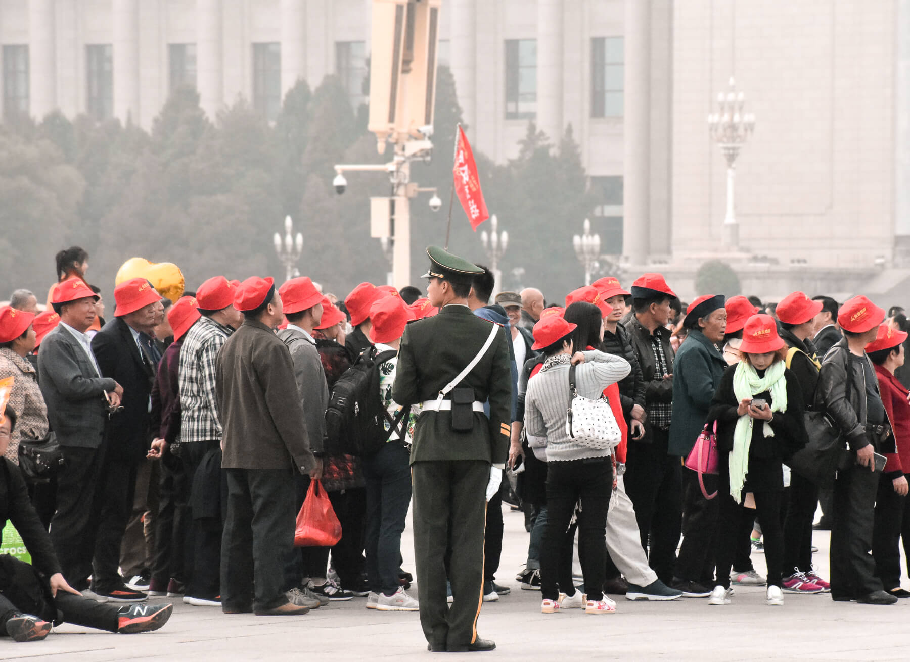 A huge group of Chinese tourists, all wearing matching red hats whilst in Tiananmen square