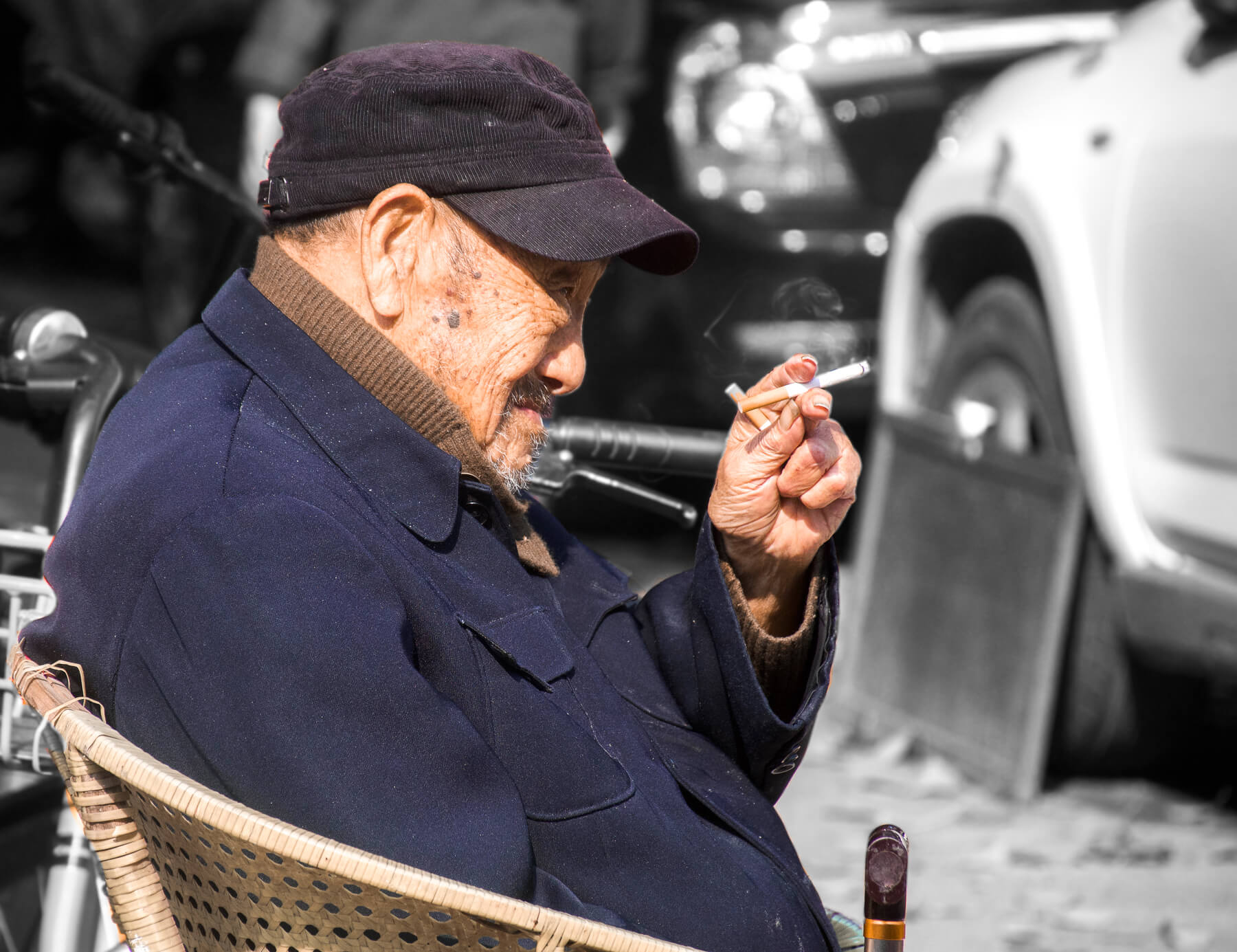 A side profile of an old Chinese man holding two cigarettes