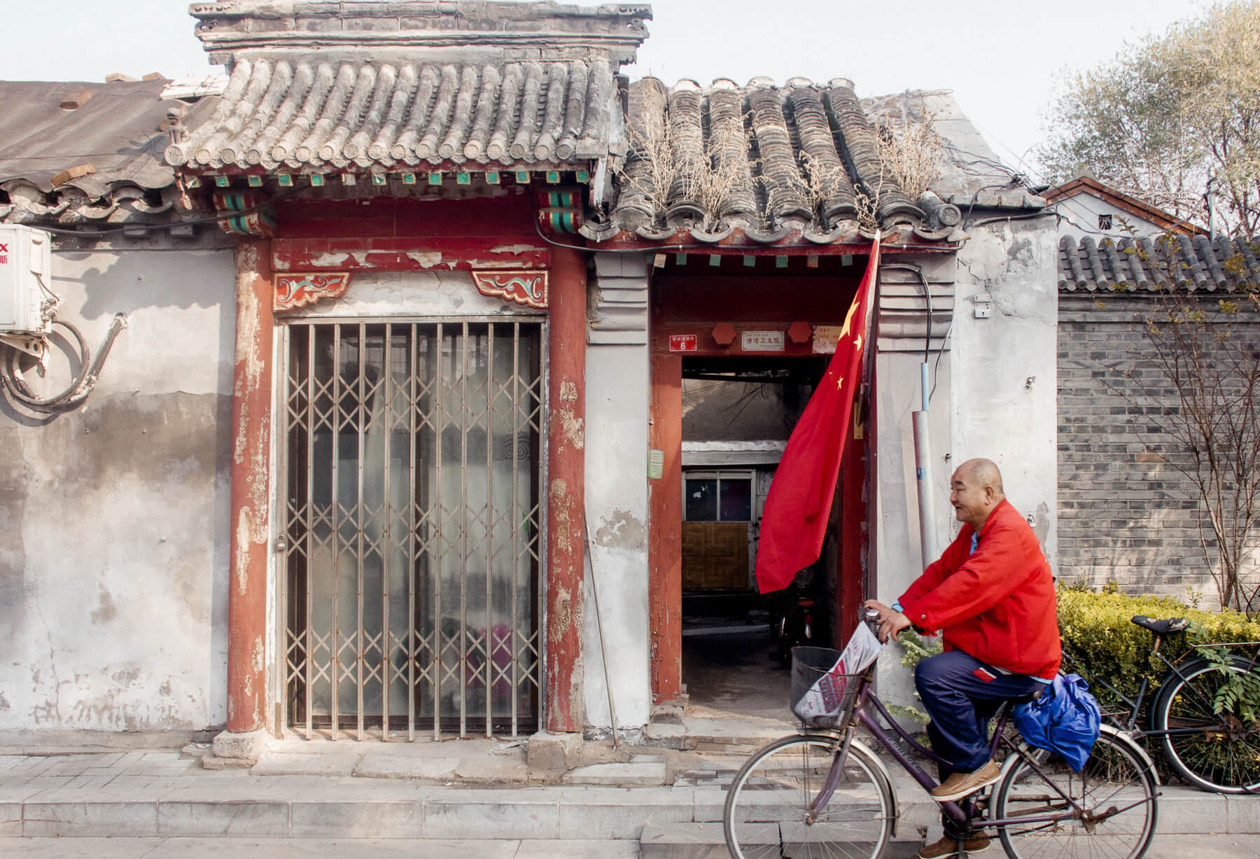 An old Chinese man riding his bicycle in front of an old traditional Hutong building and a huge China flag