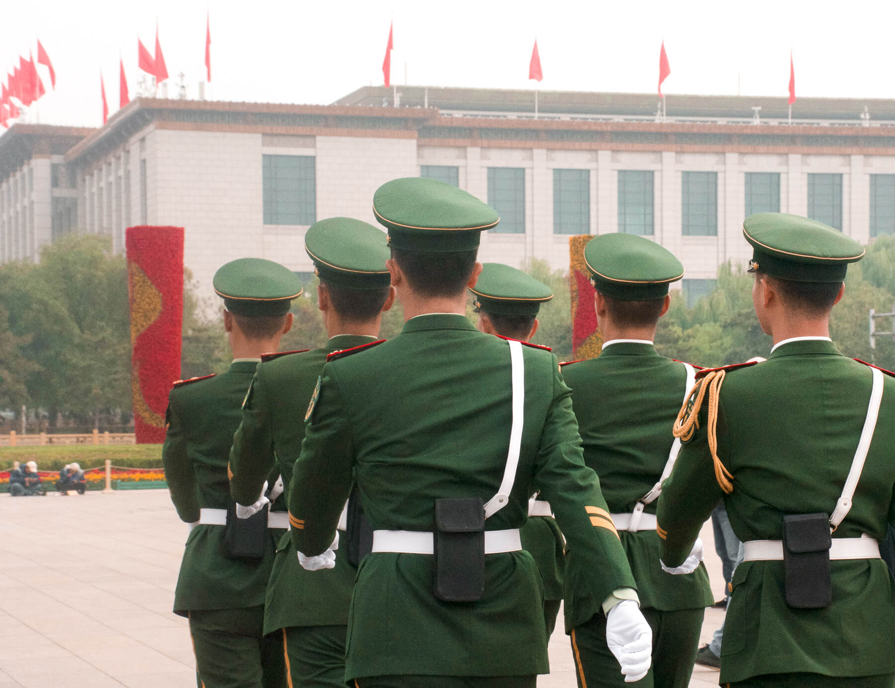 6 soldiers in their uniforms marching away from the camera with lots of China flags on the building in front of them